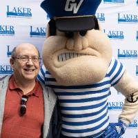 An alum poses with Louie the Laker